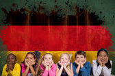 Cute pupils against germany flag — Stock Photo