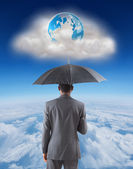 Businessman standing under umbrella — Stock Photo
