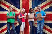 Cute pupils against union jack flag — Stock Photo
