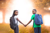 Pupils holding hands against trees — Stockfoto