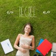 Degree against pretty student lying on grass — Stock Photo #51564943