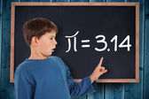 Boy pointing against blackboard — Stock Photo