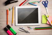 Composite image of digital tablet on students desk — Stock Photo