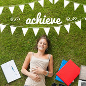 Achieve against pretty student lying on grass — Stock Photo