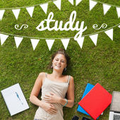 Study against pretty student lying on grass — Stockfoto