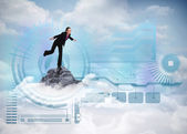 Businesswoman balancing against mountain peak — Stock Photo