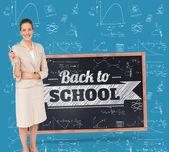 Thinking businesswoman against chalkboard — Stock Photo