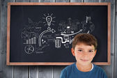 Boy smiling against blackboard — Stock Photo
