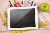 Composite image of digital tablet on students desk — Stock Photo