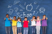 Pupils showing thumbs up against chalkboard — Stock Photo