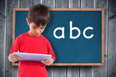 Boy using tablet against blackboard — Foto de Stock