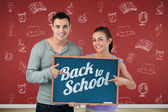 Composite image of smiling young couple pointing at sign they ar — Stock Photo