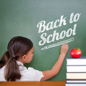 Cute pupil writing on chalkboard — Stock Photo