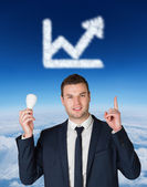 Businessman holding light bulb and pointing — Stock Photo