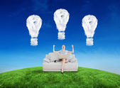 Businesswoman sitting on couch against cloud — Stockfoto