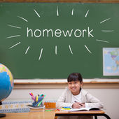 Homework against cute pupil sitting at desk — Stock Photo