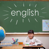 English against cute pupil sitting at desk — Stock fotografie