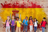 Elementary pupils running against spain flag — Stock Photo