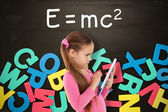 Girl using tablet against alphabet magnets — Stock Photo