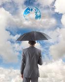 Businessman standing under umbrella — Foto Stock