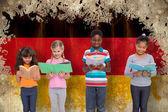Pupils reading against germany flag — Stock Photo