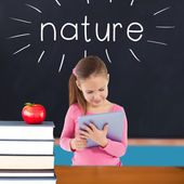 Nature against red apple on pile of books in classroom — Zdjęcie stockowe