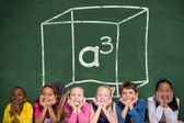 Cute pupils against green chalkboard — Stock Photo
