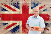 Student holding notebooks against union jack flag — Stock fotografie