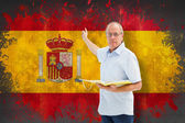 Teacher holding book against spain flag — Stock Photo