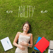 Ability against pretty student lying on grass — Stock Photo