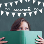 Research against student holding book — Stock Photo