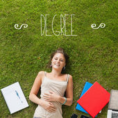 Degree against pretty student lying on grass — Stok fotoğraf
