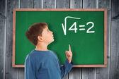 Boy pointing against blackboard — Stockfoto