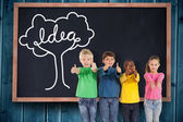 Kids showing thumbs up against blackboard — Stock Photo