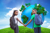 Pupils holding hands against green hill — Stock Photo
