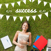 Success against pretty student lying on grass — Stock Photo
