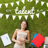 Talent against pretty student lying on grass — Stock Photo