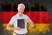 Student showing tablet pc against germany flag — Stock Photo