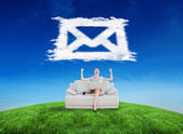Businesswoman sitting on couch against cloud email — 图库照片