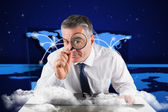 Businessman examining with magnifying glass — Stok fotoğraf