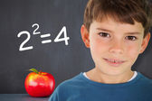 Boy against apple in front of blackboard — Stock Photo