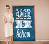 Thinking businesswoman against blackboard — Stock Photo