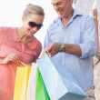 Happy senior couple looking at their purchases — Stock Photo #51591237
