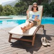Woman reading book on sun lounger by pool — Stock Photo #51591531