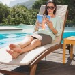 Woman reading book on sun lounger by pool — Stock Photo #51591555