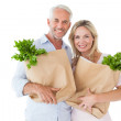 Happy couple carrying paper grocery bags — Stock Photo #51592163
