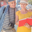 Happy tourist couple using guide book in the city — Stock Photo #51592369