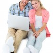 Attractive young couple sitting using laptop — Stock Photo #51592735