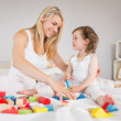 Mother and daughter playing with building blocks on bed — Stock Photo #51592763