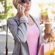 Happy mature woman walking with her shopping purchases — Stock Photo #51593171